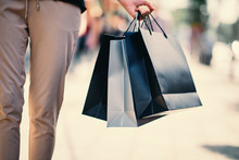 Close Up Of Woman`s Hand Holding Shopping Bags While Walking On The Street.