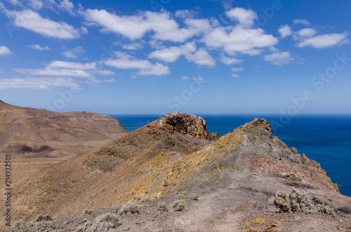 Spoed Foto op Canvas Blauwe hemel Typical landscape of Fuerteventura with barren volcanic mountains and the ocean - a view from the Entallada lighthouse terrace