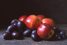 Fresh Nectarines And Plums Or Damsons On A Dark Wooden Background, Copy Or Text Space