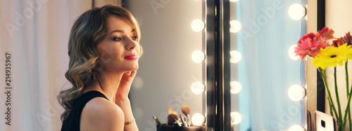 Attractive blonde girl primp at the mirror with lamps in the beauty studio Canvas-taulu
