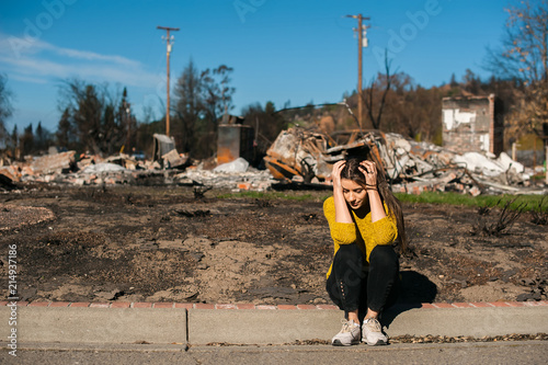 Photo Sad woman home owner holds his head by hand checking burnt out house and yard after fire disaster, consequences of fire disaster accident