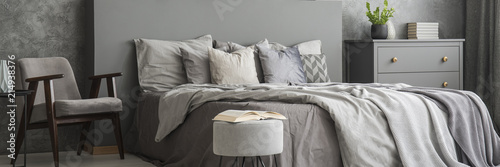 Photo Open book placed on pouf standing next to double bed with grey bedclothes in bed