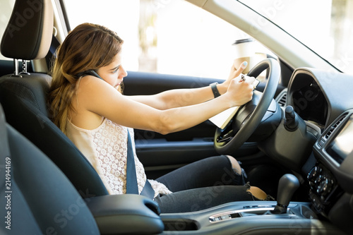 Fototapeta Woman multitasking while driving