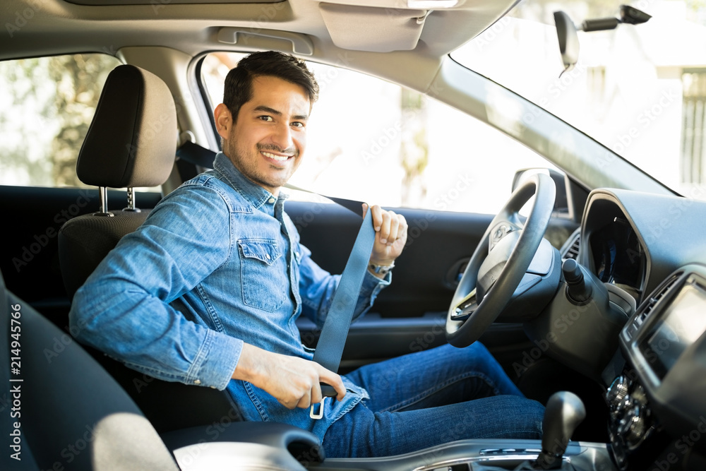 Fototapeta Man sitting in car seat fastening seat belt