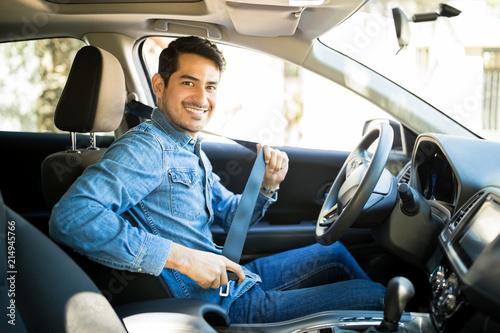Fototapeta Man sitting in car seat fastening seat belt obraz
