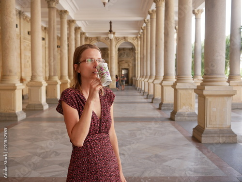 Photo Woman in a summer dress with the spa sipping jug at the Karlovy Vary spa colonnade