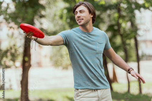 Fotomural handsome man throwing frisbee disk in park