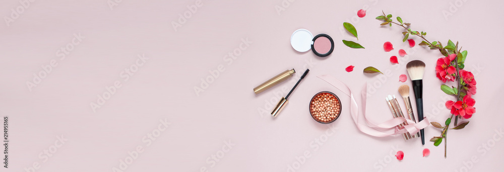 Fototapeta Various cosmetic products for make-up with red flowers on a pink background with copy space long banner. Makeup Accessories Top view Flat Lay.