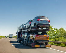 Car Carrier Trailer With New Cars On Bunk Platform. Car Transport Truck On The Highway