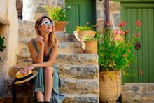 Young Redhead Girl In Green Dress On Little Village Street On Crete, Greece