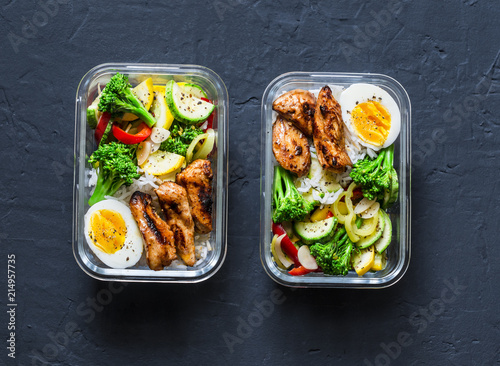 Fotografía  Rice, stewed vegetables, egg, teriyaki chicken - healthy balanced lunch box on a dark background, top view