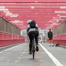 Man Riding His Bike In The Cycling Lane On Williamsburg Bridge, Brooklyn, New York City, USA.