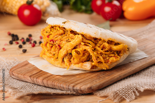 Delicious and provocative arepa with crushed chicken and around it some ingredients of its preparation