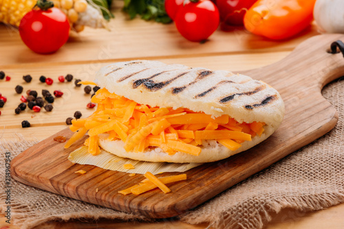 Arepa with cheddar cheese on a cutting board