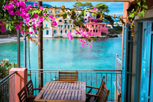 Lilac Fuchsia Blossom Flower Over Hotel Veranda In Front Of Turquoise Colored Bay Of Mediterranean Sea And Beautiful Colorful Houses Of Assos Village In Kefalonia, Greece