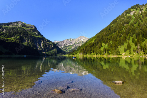 Poster Bergen Symmetrical reflections of mountain range and boat in the clear water of Lake Vilsalpsee, Tyrol, Austria