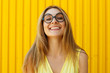 Leinwanddruck Bild Portrait of a joyful girl wearing toy funny glasses looking up over yellow background at daylight