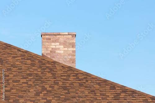 Fototapeta Red brick chimney on shingle roof od new modern house under blue sky on sunny da
