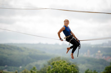 Side View Smiling Girl Sitting On The Slackline Rope
