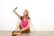 canvas print picture - Beautiful teenage girl sitting on wooden floor taking selfie shots on her cell phone. Casual young female in yellow sneakers photographs herself on smartphone, leaning on wall. Background, copy space.