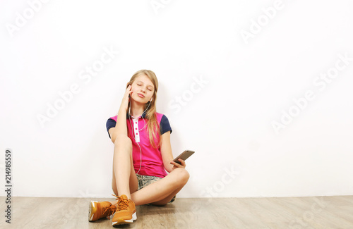 Fotografie, Obraz  Beautiful teenage girl sitting on wooden floor listening favorite song on mobile music app from her cell phone