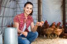 Portrait Of Young Woman Farmer Holding Fresh Eggs In Hands In Henhouse