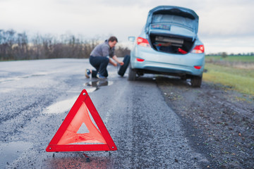 The man is changing the damaged wheel of the car on the roadside of a bad road after the rain against the background of an orange  emergency  triangle warning