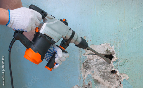 Fototapeta The builder with hammer drill perforator equipment making hole in wall at construction site