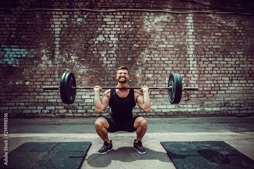 Fotografia, Obraz  Muscular fitness man doing deadlift a barbell over his head in outdoor, street gym