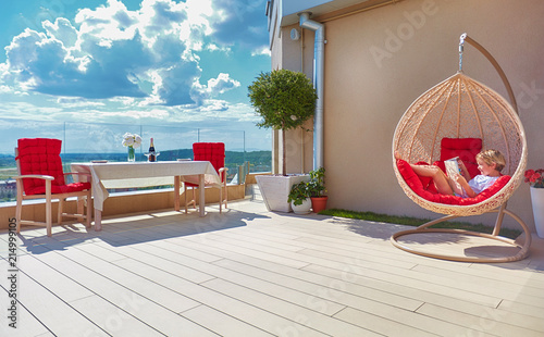 Stampa su Tela young boy relaxing in hammock on modern rooftop patio, home terrace