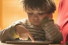 Boy Using Digital Tab At Home