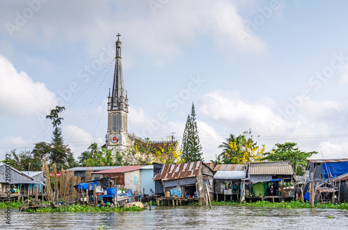 Fototapeta  One of the banks of the Mekong river with the Cathedral of Cai Be, a river-land