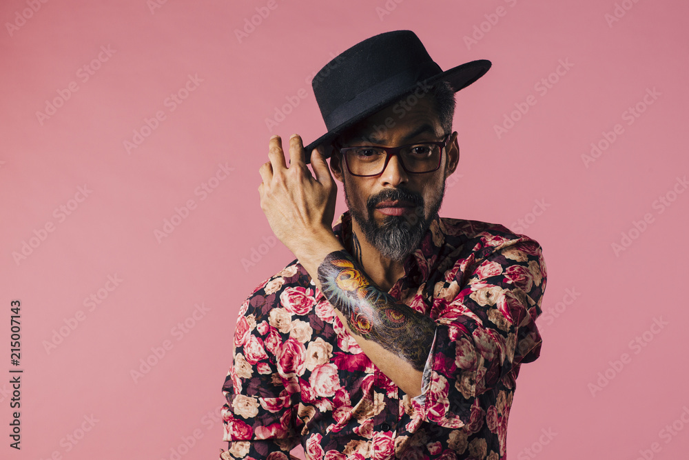 Fototapety, obrazy:  Portrait of a very cool mature artist with tattoo and glasses, touching his hat, isolated on pink studio background
