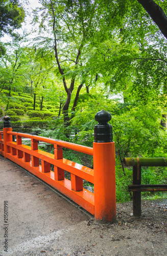 Papiers peints Corail A partial view of an orange painted wooden bridge in the park or garden of Fushimi inari Teisha shrine in Kyoto, Japan, during a summer day in rainy season