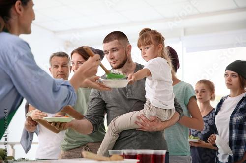 Volunteers serving food for poor people indoors Canvas Print