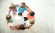 canvas print picture - Little children making circle with hands around each other indoors, top view. Unity concept