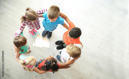 Valokuva  Little children making circle with hands around each other indoors, top view