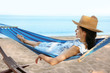 Young woman resting in comfortable hammock at seaside