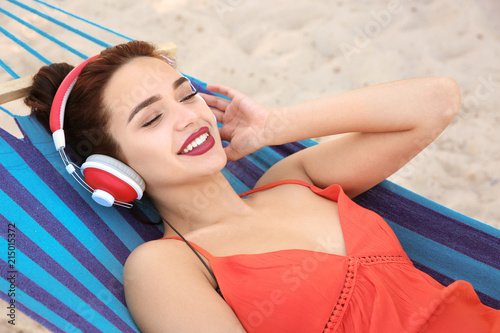 Young woman listening to music in comfortable hammock at seaside - 215015372