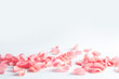 Beautiful rose petals scattered on light background