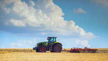 In The Summer Heat Of The Tractor Plows The Field After Harvest Against The Bright Sunny Sky With Clouds.