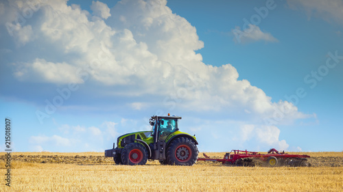 Keuken foto achterwand Cultuur In the summer heat of the tractor plows the field after harvest against the bright Sunny sky with clouds.