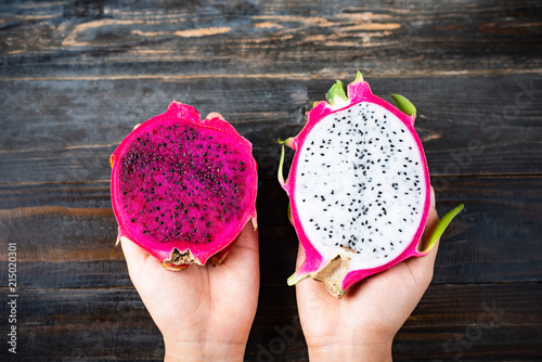 Half red and white dragon fruit holding by hand on wooden background, top view - 215020301