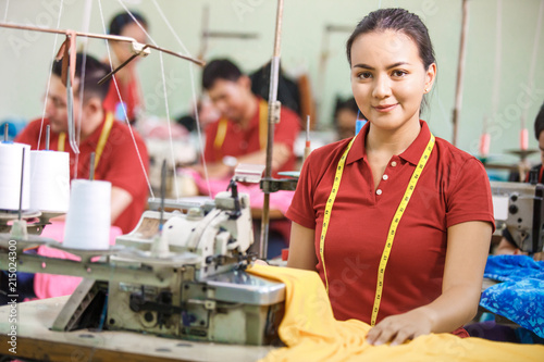 Obraz Seamstress in textile factory smiling while  sewing with industr - fototapety do salonu