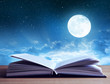 Leinwanddruck Bild - Open book on wooden plank night sky with moon in the background.