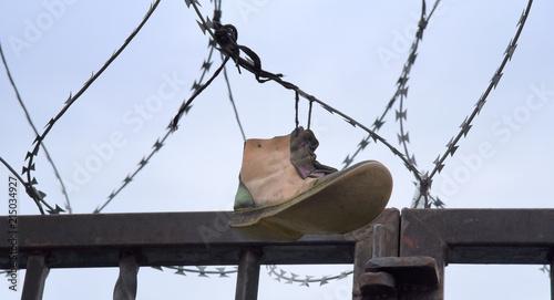 Canvastavla Verlorener Schuh im Stacheldraht über einem Grenzzaun