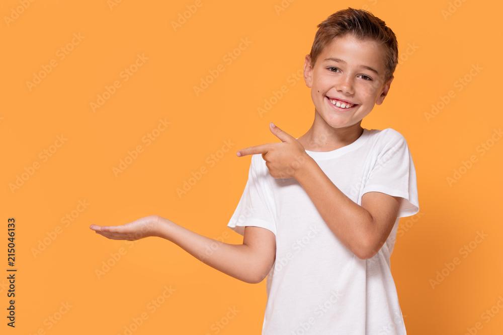 Fototapety, obrazy: Young emotional little boy on orange studio background.