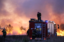 Team Of Fire Fighters Fighting Fire In The Evening. Fire Truck On The Flames And Smoke Background.