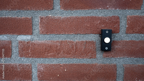 Fotografia, Obraz background of a red stone wall with a black with white doorbell button