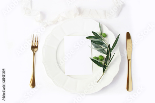 Festive table summer setting with golden cutlery, olive branch, porcelain dinner plate and silk ribbon on white table background Fototapete